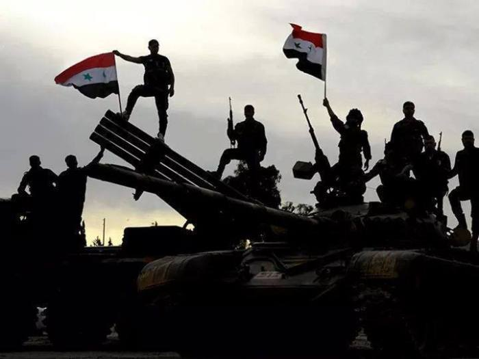 Soldats syriens debout sur un char et un lance-roquettes multitubes, arborant des drapeaux. Une majorité d'analystes a sous-estimé cette armée dont la doctrine semble d'un autre temps.  En quatre années de conflit, l'armée syrienne s'est adaptée et a intégré des techniques de combat asymétriques en incluant les unités du Hezbollah libanais. Ce dernier ayant  acquis lors de ce conflit la capacité de manoeuvre sur un large front.